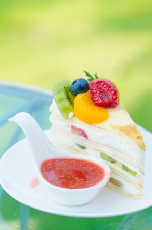 sweet cake with fruits on plate and green background Stock Photo - 18506674