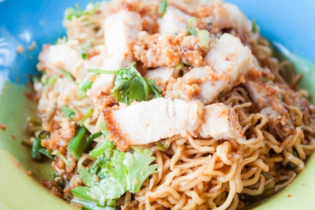 Close up crispy pork on stir fried spicy noodles photo