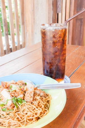 Simple meal with stir fried spicy noodles and cola photo