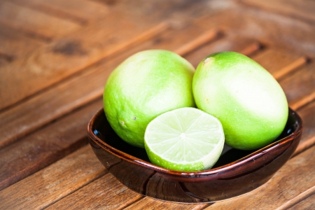 wholes: Fresh lime wholes and slice on wood background