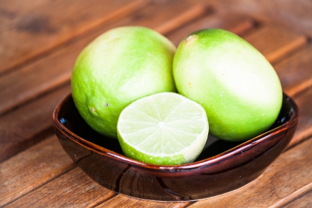 wholes: Fresh lime wholes and slice on wood table