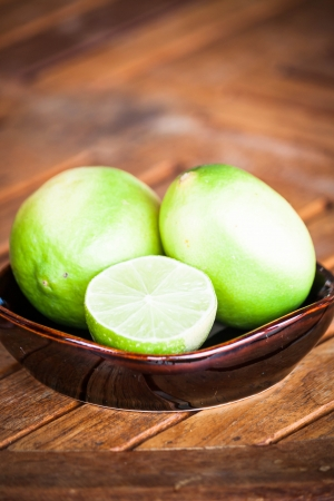 wholes: Fresh citrus lime wholes and slice on wood table Stock Photo