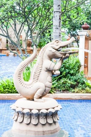 Crocodile statue spray water decorated blue pool