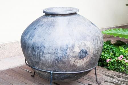 Vintage ceramic water jar decorated green garden Stock Photo