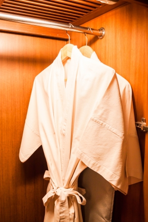 White robes with wooden hangers in hotel wardrobe Stock Photo - 20479431