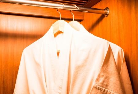 Bathrobes hanging on wooden hangers in wardrobe Stock Photo - 20479430