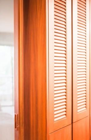 Wooden closet and translucent mirror partition in the room photo