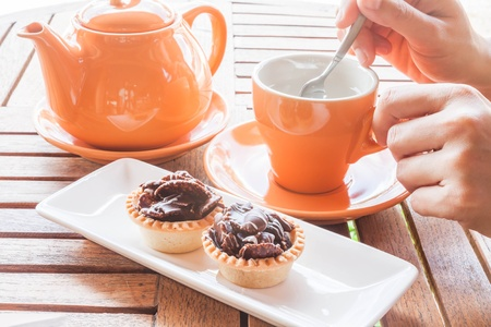 Hot cup of white tea and crispy chocolate tarts, stock photo photo