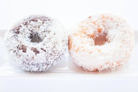 Chocolate and vanilla coconut donuts on white plate, stock photo photo