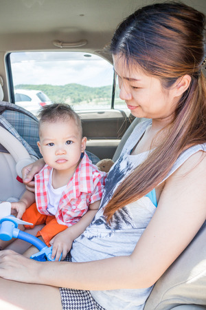 Asian boy sitting in the car with his mother, stock photo photo
