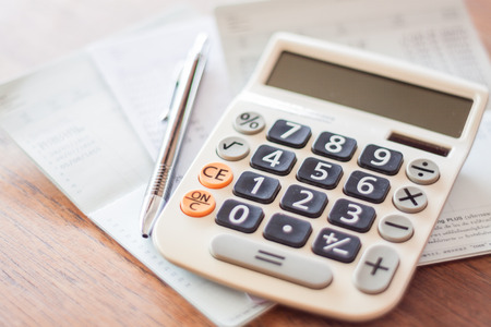 calculator chinese: Calculator and pen on bank account passbook, stock photo
