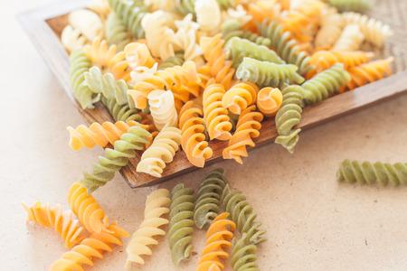 fusilli: Raw fusilli pasta on wooden tray, stock photo