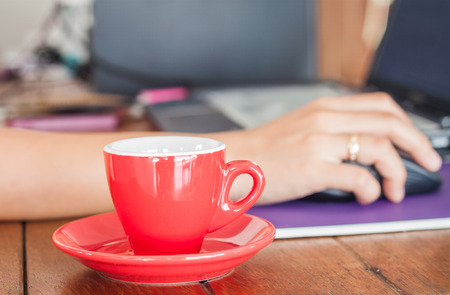 work station: Red coffee cup on work station, stock photo