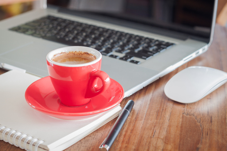 Red coffee cup with notepad and laptop, stock photo