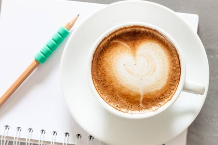 Coffee cup with notepad on grey background, stock photo