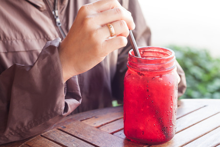 non alcoholic beverage: Iced drink in red glass on wooden table with vintage filter, stock photo