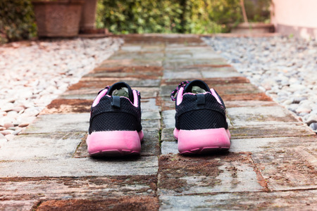 foot path: Running shoes in home garden foot path, stock photo