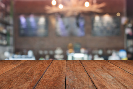 Brown table top with blurred coffee shop interior for background