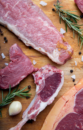 Raw beef barbecue with rosemary, garlic and pepper on cutting board on wooden background