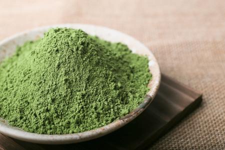 Polvo de té verde en el plato, estilo natural. Concéntrese en el polvo de té verde.