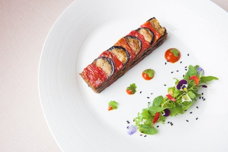 Lamb and eggplant grill with wild rocket salad, France menu on white dish 스톡 콘텐츠