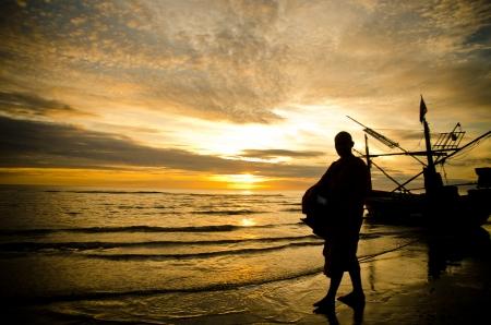 Silhouettes of monks on the beach,Hua Hin Thailand photo