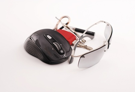 Eyeglasses with keys and mouse in white background photo