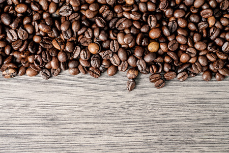 Coffee beans concept on wooden table background. Top of view.