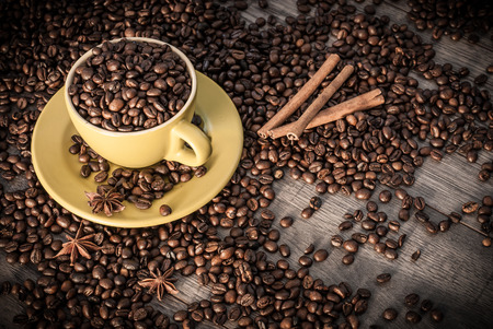 mocca: Coffee cup with coffee beans on wooden table background with cinnamon and star anise.