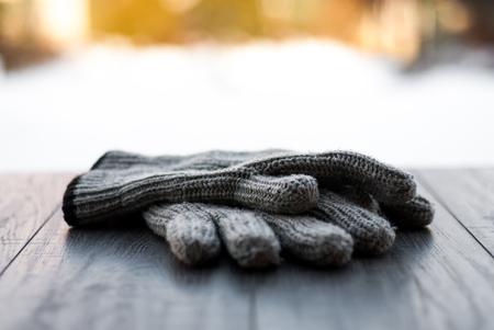 Gloves winter scene on wooden desk background.