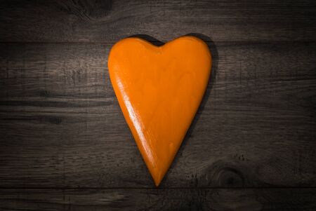 Valentines day celebration concept background. Orange hearth on wooden background table.