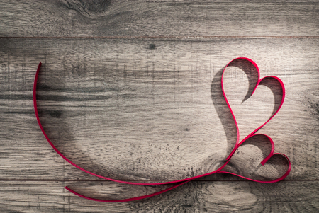 Valentines day celebration concept on wooden background table. Two ribbon hearths. Top view.