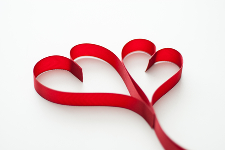 Valentines day celebration concept background. Red ribbon hearths on white background isolated. Reklamní fotografie