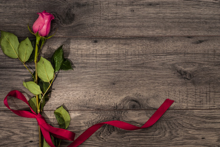 Valentines day celebration concept background. Rose and hearths on wooden background table. Top view. Reklamní fotografie