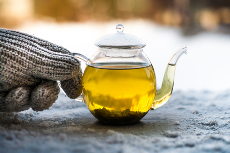 Tea with snow on wooden background and gloves.