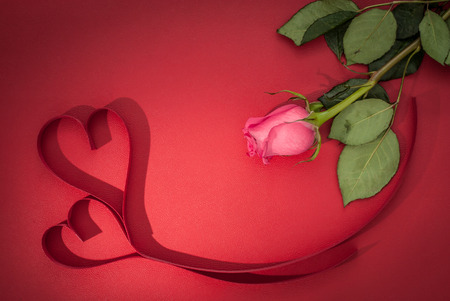 Valentines day celebration concept background. Rose and hearths on red background table. Top view.