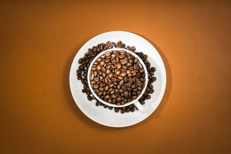 Coffee cup with coffee beans on brown, orange background.
