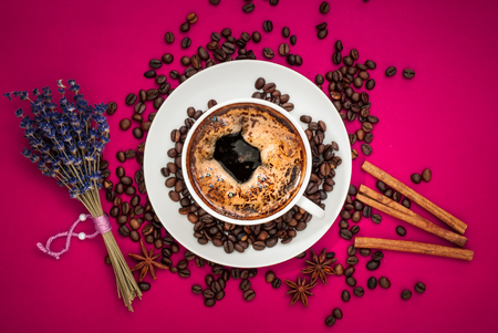 Coffee cup with coffee beans on wooden table background with cinnamon and star anise.