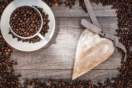 Coffee cup with coffee beans on wooden table background with wooden heart.