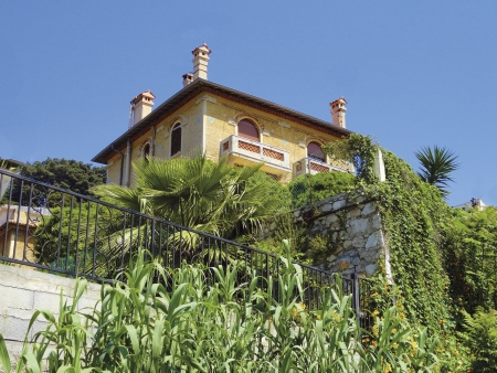 Yellow mediterranean mansion with vegetation