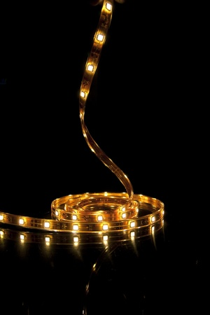 Glowing LED garland on black background photo
