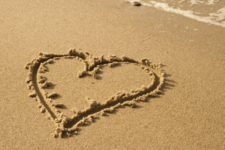 heart on the sand: handwritten heart on sand with wave approaching Stock Photo