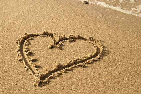 ručně psané srdce na písku s vlnou se blíží