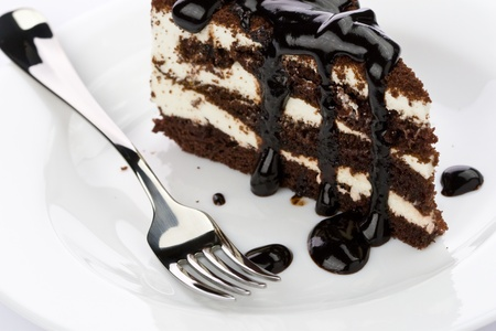 custard slices: Piece of chocolate cake with icing on white plate Stock Photo