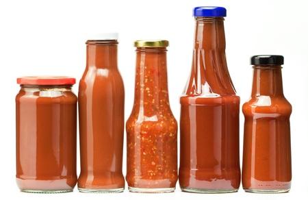salsa de tomate: cuatro botellas de ketchup aislados en blanco