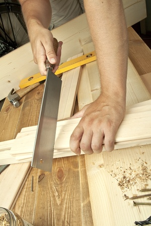 Man sawing plank on a wooden background. photo