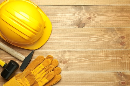 construction helmet: Different tools on a wooden background.
