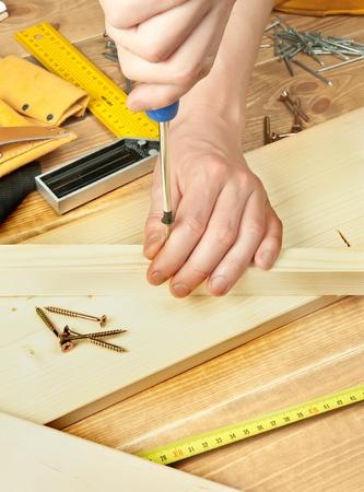 herramientas de carpinteria: Tornillo de manos del hombre atornillado en un puntal