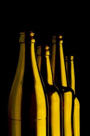 Four brown bottles on black background photo