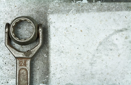 Old rusty wrench on metal background photo